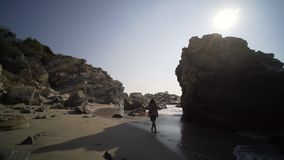 Follow the young women. Pov , follow the young women, in silhouette walking on beach with big cliff in sun shine stock footage