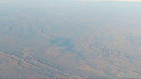 POV från flygplanfönstret som visar röd den jordbergskedja och sjön mitt- ram lager videofilmer
