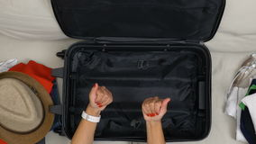 POV of girl with red polished nails having a dilemma and trying to decide what to pack for trip looking at suitcase. Point of view of girl with red polished stock footage