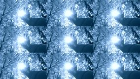 POV of hand of man who moves it in air, through fingers through rays. Of sun that shines through leaves of tree. Blue and white color. Multicam split screen stock video footage