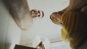 POV of happy couple kissing while opening cardboard box after relocation and looking inside and taking things in new. POV of Cheerful happy couple kissing while Royalty Free Stock Photo