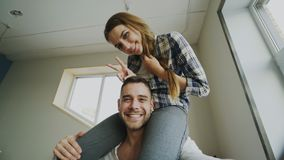 POV of happy smiling and beautiful couple take selfie portrait on smartphone camera while girl sitting on man`s neck at Royalty Free Stock Photos