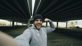 POV of Happy sportive man taking selfie portrait with smartphone after training in urban outdoors location in winter. Season stock footage