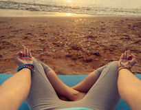 POV image of woman meditating in pose of lotus. Young woman meditating in pose of lotus on beach at sunset in summer, point of view Royalty Free Stock Image