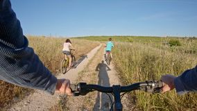 POV of two kids enjoying a bicycle ride on the countryside with their father stock footage