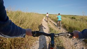 POV of two kids enjoying a bicycle ride on the countryside with their father stock video