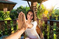 Pov-kvinna som ger höjdpunkt fem till den gladlynta flickan för man i morgonhandgest, medan sitta på tabellen på sommarterrass Fotografering för Bildbyråer