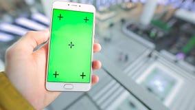 POV, männlicher Handholding Smartphone mit grünem Schirm im Aufzug des Einkaufszentrums stock video