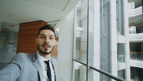 POV młody biznesmen w kostiumu ma online wideo gadkę używać smartphone kamerę i opowiadający jego koledzy wewnątrz zbiory