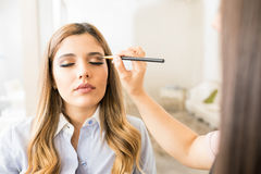 POV of a makeup artist at work. Point of view of a makeup artist adding some eyeshadow to a beautiful female customer in a beauty salon Royalty Free Stock Photos