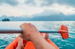 POV of Man floating in kayak holding paddle during early morning tour. Khao Sok national park, Cheow Lan lake, Thailand stock photos