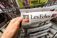 POV man holding Les Echos newspaper with Stephen Hawking portra. PARIS, FRANCE - MAR 15, 2018: POV man holding Les Echos newspaper with Stephen Hawking portrait royalty free stock photos