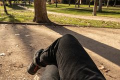 POV of a man legs crossed sitting on a bench in an outdoor park royalty free stock photo