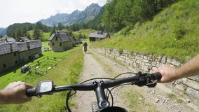 POV man riding e-bike to town village.Mtb action cyclist exploring path near mountains.Electrical bike active people. Sport travel vacation in Europe Italy Alps stock footage