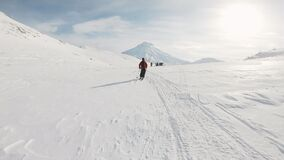 Pov man with snowboard walking on mountain. Group expedition in front on skies moving on pure white snow. Magnificent
