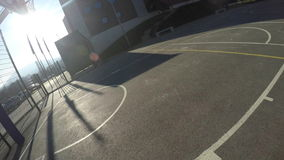 POV Man throwing ball on hoop on basketball court stock footage