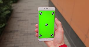 POV manlig handinnehavsmartphone med den tomma skärmen som går i stad