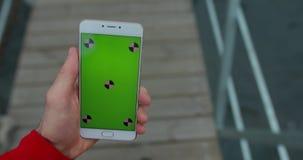 POV, mannelijke smartphone van de handholding met het lege scherm die in stadspijler lopen