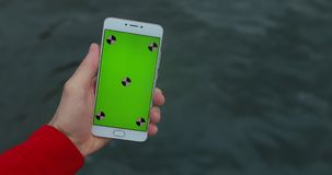 POV, mannelijke smartphone van de handholding met het lege scherm, overzeese achtergrond