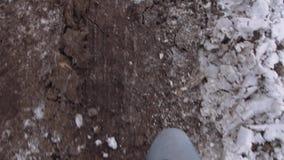 POV-mens die in donkere laarzen op vuile weg bij de winter lopen stock video