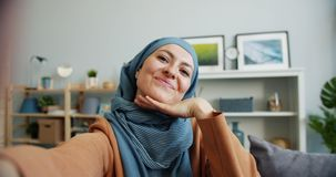 POV of Middle Eastern woman in hijab taking selfie at home looking at camera stock video footage