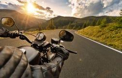 POV motorbiker держа бар управления рулем, катание в Альпах Стоковое Фото