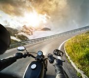 POV of motorbiker holding steering bar, riding in Alps Stock Photography