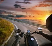 POV of motorbiker holding steering bar, riding in Alps Stock Image