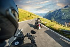 POV of motorbiker holding steering bar, riding in Alps Royalty Free Stock Photo