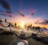 POV of motorcycle driver holding handlebar, heading to modern ci Royalty Free Stock Image