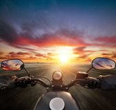 POV of motorcycle driver holding handlebar, heading to modern ci Stock Image