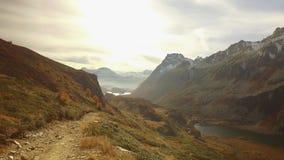 POV odprowadzenie na spadek ścieżce drewna, dolinny jezioro i śnieżne góry przy zmierzchem z racą, Pogodny jesień dzień Wycieczku zdjęcie wideo