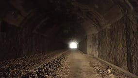 Pov odprowadzenie wśrodku starego zmroku długiego zaniechanego tunelu z jaskrawym światłem w końcówce zbiory
