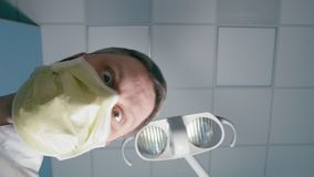POV of Patient during Visit at Dentist is Working in the Dental Hospital. POV of Patient during Visit at Funny Doctor Dentist in Mask Working Doing a Surgery in stock video