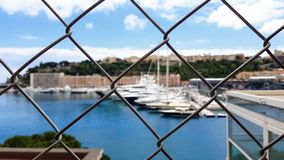 Pov of poor tourist, viewing yachts behind fence, lack of money for luxury rest. Stock photo stock photos