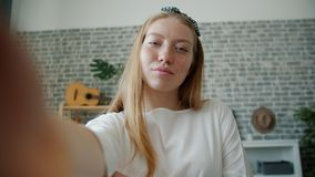 POV portrait of happy girl taking selfie holding camera at home posing stock video
