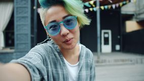 POV of pretty Asian hipster making online video call talking looking at camera. POV of pretty Asian girl hipster making online video call talking and smiling stock video
