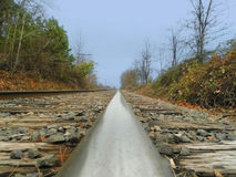 POV Railroad. A point-of-view shot of railroad tracks at the far end of town during a light rain Stock Photo