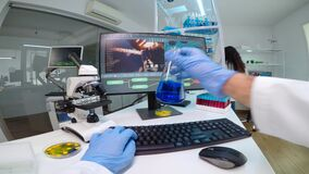POV of scientist doctor doing research checking liquid from chemical container