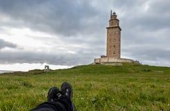 POV se trouvant en tailleur sur l'herbe observant un phare en pierre dans un Coruña, Galicie, Espagne images libres de droits