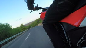 POV shot of from a fast motorcycle driving on a curved road. POV shot of from fast motorcycle driving on a curved road at high speed stock video footage