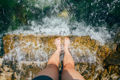 POV shot of female feet and legs in water. View from top of camera of person making photos of legs standing on pier or step and waves rolling over, beautiful Stock Images