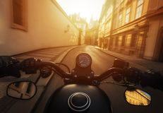 POV shot of man riding on a motorcycle. Hands of motorcyclist on a streets of Prague historical centre, Czech republic. stock photo