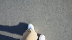 POV shot of a man`s feet walking on the sidewalk with white sneakers in broad daylight