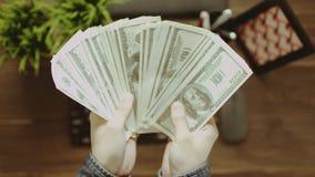 POV shot of man throwing dollars down on table