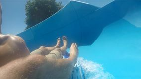 POV shot of two guys using slide in water park. POV shot of two young men using slide in water park or aquapark, having a good time stock video footage