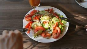 Pov-sikt av den unga kvinnan för händer i den röda klänningen som har matställen i ett kafé Ny sallad med tomater, gurkor, chees arkivfilmer