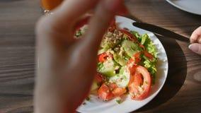 Pov-sikt av den unga kvinnan för händer i den röda klänningen som har matställen i ett kafé Ny sallad med tomater, gurkor, chees stock video