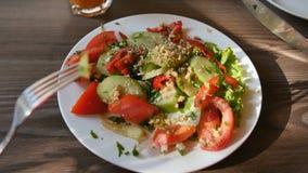 Pov-sikt av den unga kvinnan för händer i den röda klänningen som har matställen i ett kafé Ny sallad med tomater, gurkor, chees lager videofilmer