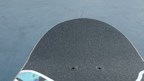POV skateboard dropping in on curved ramp. At skatepark stock video footage